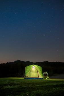 Prachtig landschap van prachtige nachtelijke hemel met sterren boven tentenkamp, reizen en kamperen concept