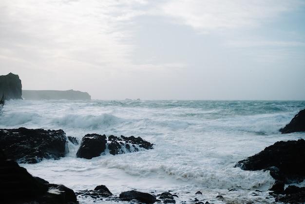 Prachtig landschap van zeegolven die breken over rotsformaties