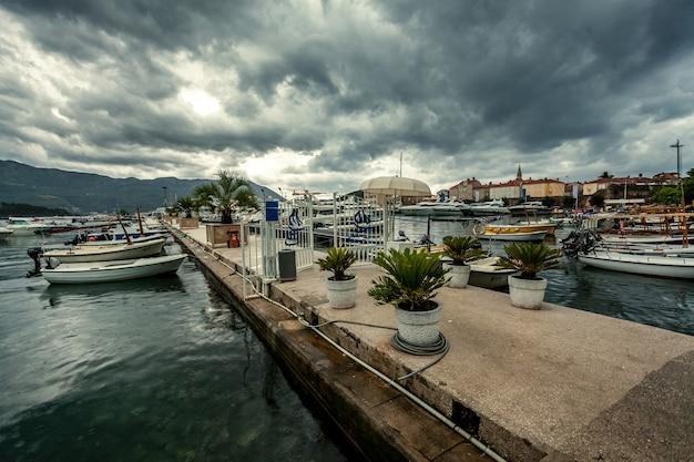 Prachtig landschap van zeehaven met afgemeerde jachten op regenachtige dag