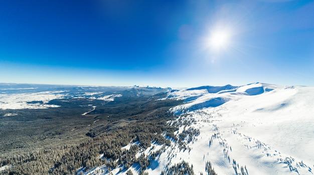 Prachtig luchtfoto van de bergketens op een zonnige ijzige winterdag
