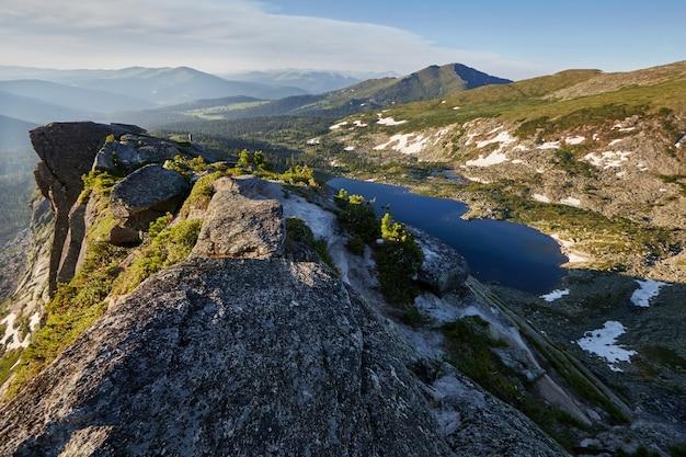 Prachtig meer in de bergen in de avondzon. zonsondergang in de fabelachtige bergen, het meer gevormd door een instorting van de steen. lente in de bergen