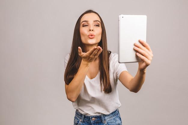 Prachtig meisje dat luchtkus verzendt tijdens videogesprek. lieve vrouw met behulp van digitale tablet