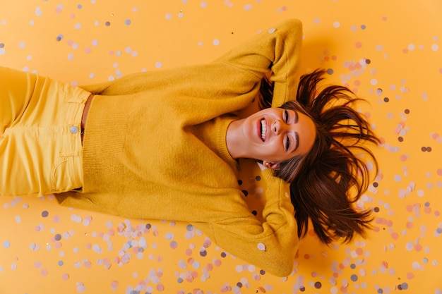 Prachtig meisje in gele broek liggend op paarse confetti. overhead portret van enthousiaste emotionele vrouw.