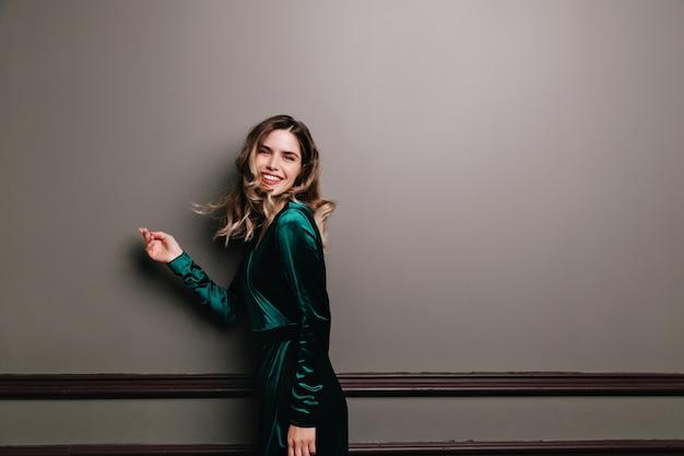 Prachtig meisje in groene fluwelen jurk genieten van fotoshoot. enthousiaste jonge vrouw met golvend bruin haar lachend