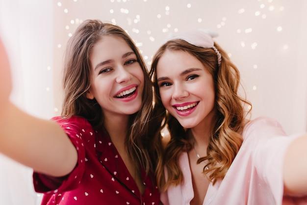 Prachtig meisje in katoenen rode pyjama selfie maken met vriendin. extatische europese dame die een foto van zichzelf neemt, die zich in de buurt van zus in oogmasker bevindt.