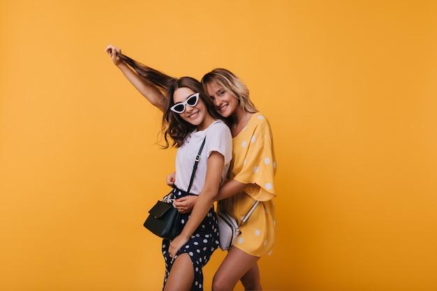 Prachtig meisje in wit t-shirt spelen met haar haar terwijl poseren met beste vriend. indoor portret van schattige zusters positieve emoties te uiten.