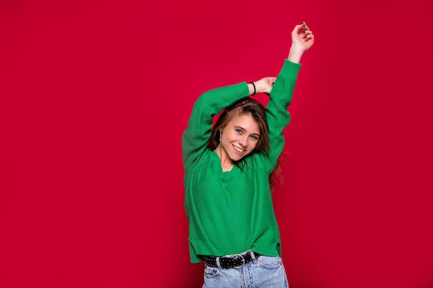 Prachtig meisje met lang haar dansen met een glimlach op rode achtergrond. indoor portret van geïnspireerde blanke dame in winter outfit gelukkige emoties uitdrukken.