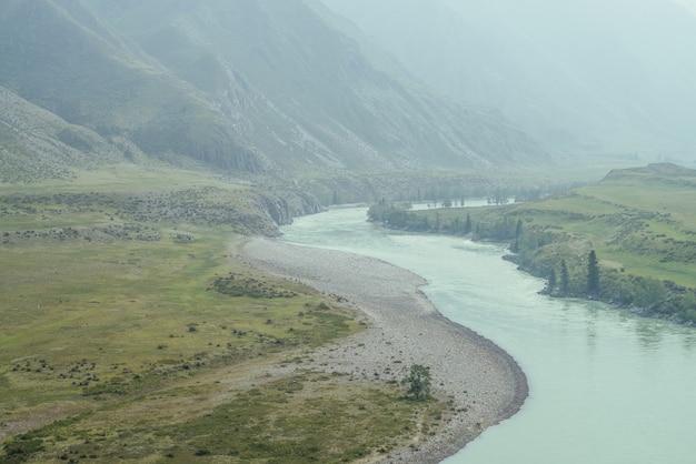 Prachtig mistig berglandschap met brede bergrivier. donkergroen somber landschap met grote bergrivier in mist. donker sfeervol uitzicht op de grote rivier tussen de grote bergen bij regenachtig weer.