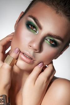 Prachtig model met een gezonde huid en coole make-up die de camerastudio van dichtbij bekijkt
