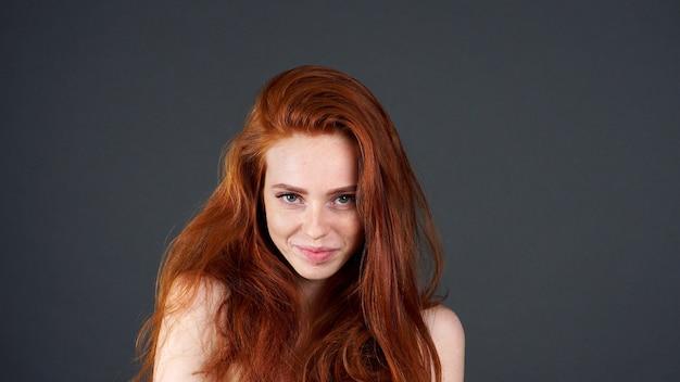 Prachtig model met glanzend recht lang rood haar.