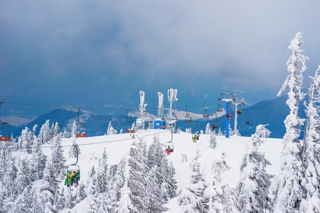 Prachtig onderaanzicht van de kabelbanen boven een pittoreske besneeuwde helling met bomen op een bewolkte winterdag.