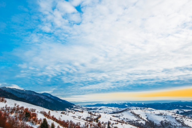 Prachtig panorama van berghellingen met paden met uitzicht op de heuvels en naaldbossen bewolkt en ijzig op een winteravond. wintertoerisme en recreatie concept.