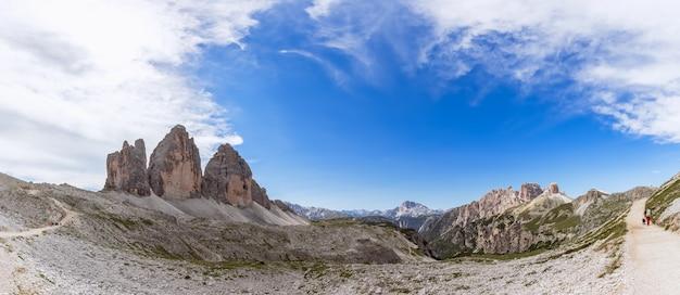Prachtig panorama van tre cime di lavaredo en toerist met zijn hond die langs het pad loopt