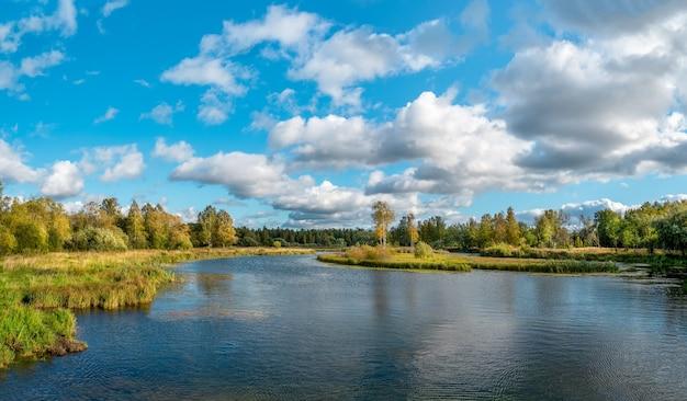 Prachtig panoramisch herfstlandschap met heldere bomen aan de oever van het meer.