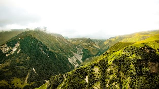 Prachtig panoramisch uitzicht vanaf de met gras begroeide heuvel naar de kazbek-bergen.