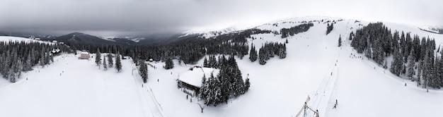 Prachtig panoramisch uitzicht vanaf een hoog punt op de skibasis met kabelbanen op een bewolkte winterdag