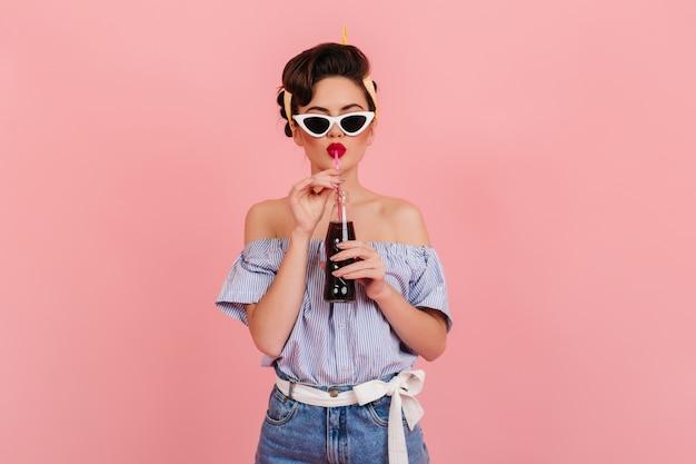 Prachtig pinupmeisje dat drank met plezier drinkt. vooraanzicht van geweldige brunette vrouw staande op roze achtergrond.
