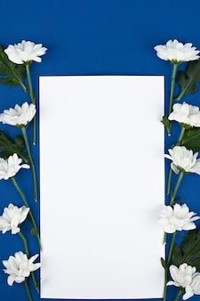 Prachtig rechthoekig bloemstuk van witte bloemen met een blanco vel papier