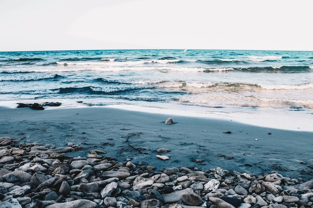 Prachtig rots- en zandstrand van de zee met medium golven onder een heldere blauwe hemel