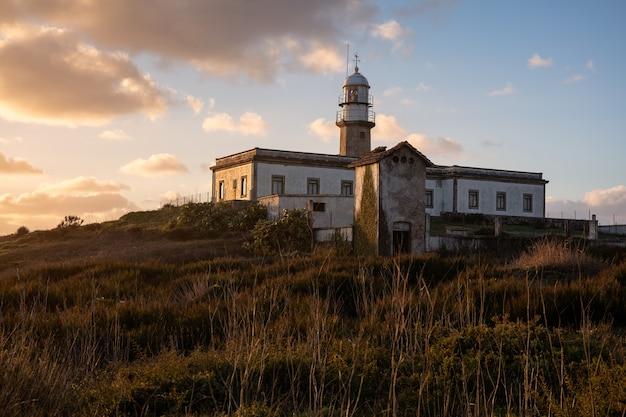 Prachtig schot van de larino-vuurtoren in galicië, spanje tijdens zonsondergang