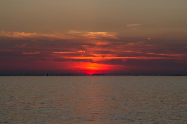 Prachtig shot van de zee met een rode lucht in de verte