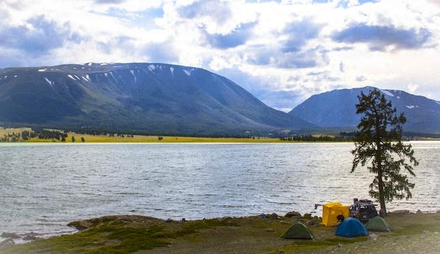 Prachtig shot van een blauwe bewolkte hemel en een bergketen en een meer op een koele dag