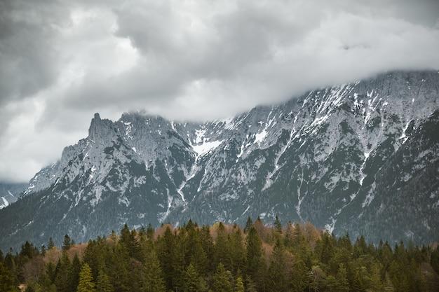 Prachtig shot van een hoge berg bedekt met dikke witte wolken