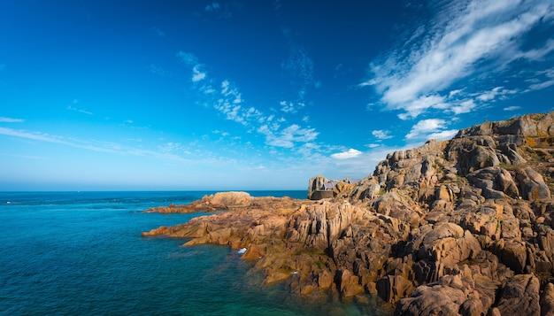 Prachtig shot van een kalme zee met heuvels en kliffen aan de rechterkant