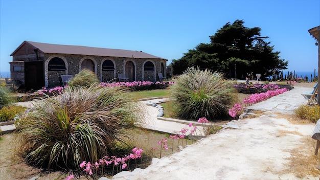 Prachtig shot van een stenen gebouw met een mooie tuin onder de blauwe lucht in punta de lobos, chili