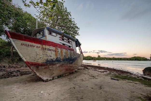 Prachtig shot van een verlaten boot achtergelaten aan de kust