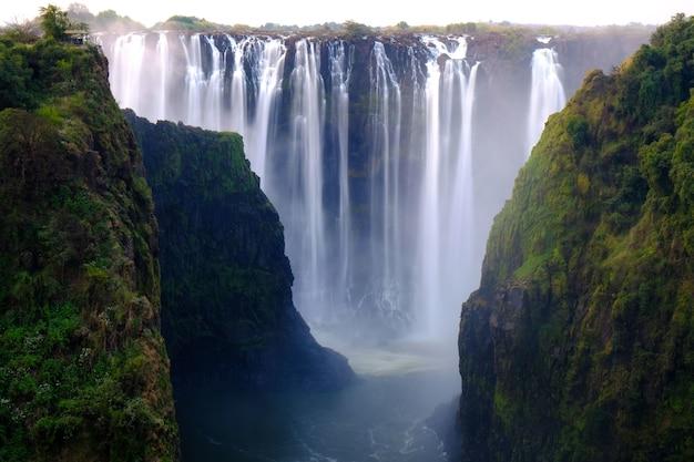 Prachtig shot van een waterval omgeven door bomen en heuvels