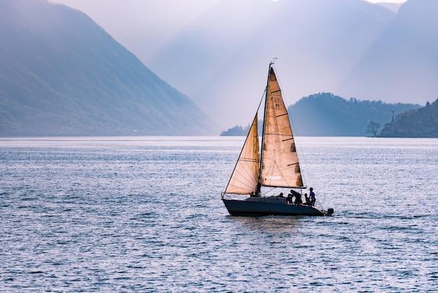 Prachtig shot van een zeilboot die over de zee vaart, omringd door bergen