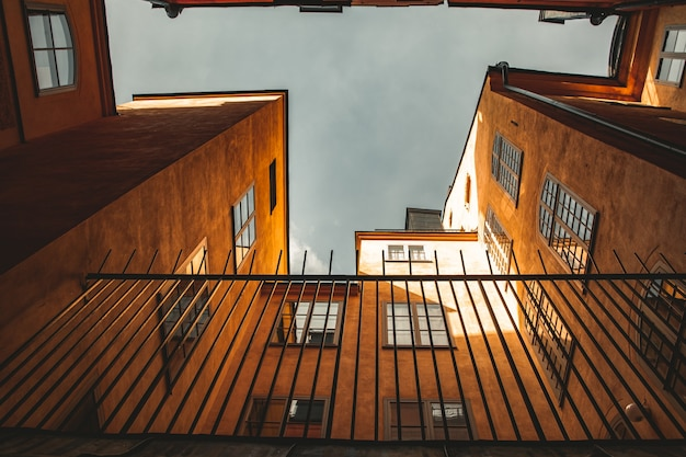Prachtig shot van onderen van oranje gebouwen en een hek ervoor