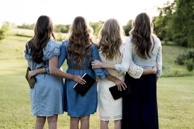 Prachtig shot van vier meisjes met hun armen om elkaar heen terwijl ze de bijbel vasthouden