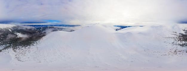 Prachtig skipanorama van glooiende heuvels en bergen in de sneeuw met toeristenkampen op een winterdag