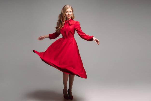Prachtig slank model in felrode jurk en zwarte hakken.