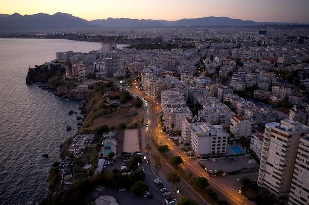 Prachtig stadsbeeld en zee bij zonsondergang. stadsgebouwen in de buurt van de kust. bovenaanzicht van drone.
