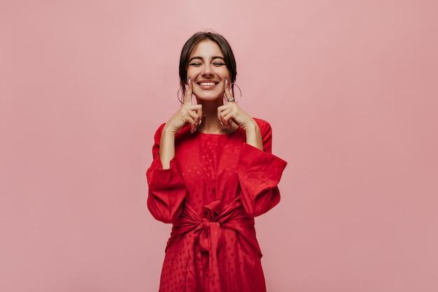 Prachtig stijlvol meisje met brunette kapsel in heldere trendy jurk glimlachend en poserend met gesloten ogen op geïsoleerde muur