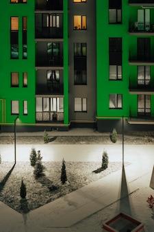 Prachtig terras in een kleurrijk groen appartementencomplex сovered in sneeuw.
