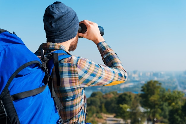 Prachtig uitzicht. knappe jonge bebaarde man die rugzak draagt en door een verrekijker kijkt