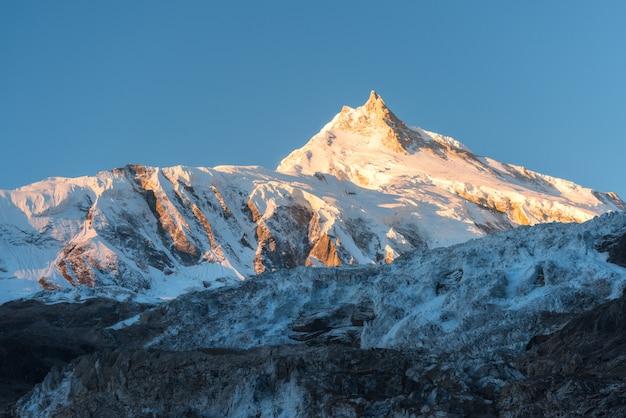 Prachtig uitzicht op besneeuwde berg bij kleurrijke zonsopgang in nepal