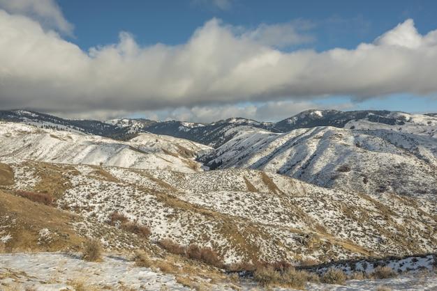 Prachtig uitzicht op besneeuwde bergen met een blauwe bewolkte hemel overdag