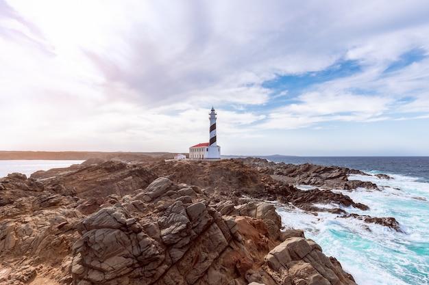 Prachtig uitzicht op de beroemde vuurtoren faro de favaritx onder de hemel met wolken op het eiland menorca, balearen, spanje