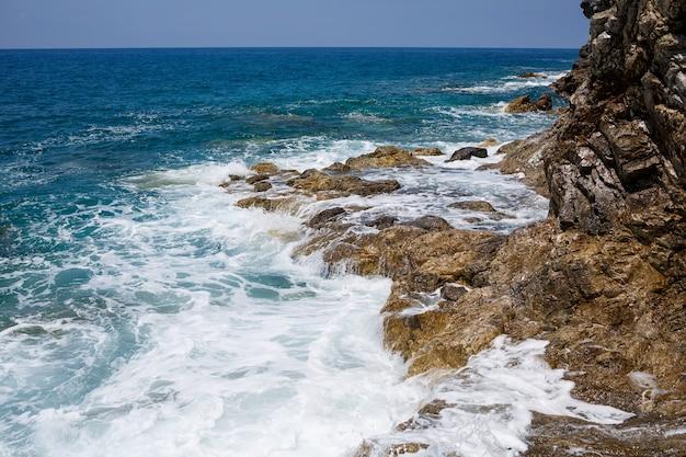 Prachtig uitzicht op de blauwe middellandse zee. zonnige rotsen, golven met schuim en opspattend water. de golf slaat tegen de rotsen aan de kust