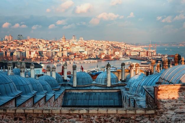 Prachtig uitzicht op de gouden hoorn bij zonsondergang, istanbul, turkije. de daken van de suleymaniye-moskee in de stralen van de ondergaande zon tegen de blauwe zee in istanbul