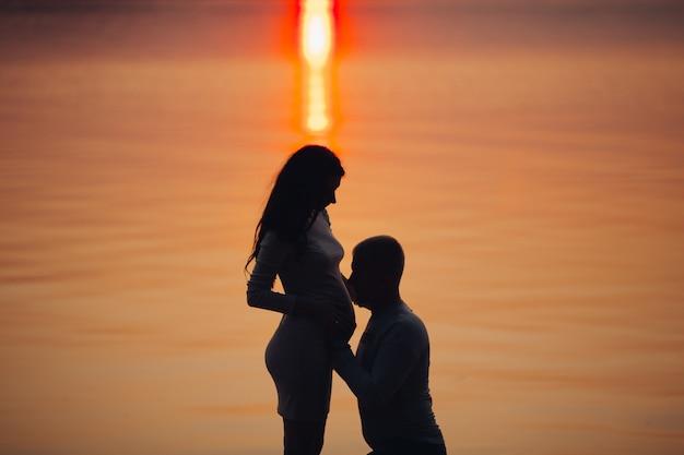 Prachtig uitzicht op de man omarmen de buik van zijn vrouw tegen de zee