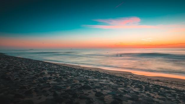 Prachtig uitzicht op de oceaan bij zonsondergang gevangen in zeeland, nederland