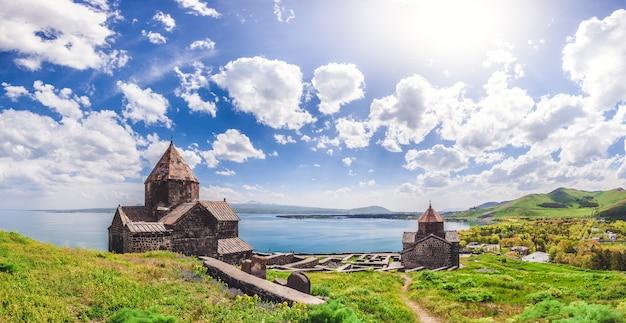 Prachtig uitzicht op de oude kerk tegen de prachtige blauwe bewolkte lucht en het meer