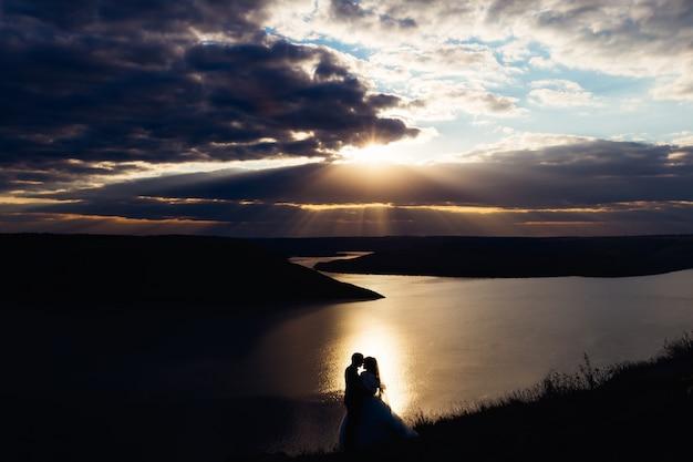 Prachtig uitzicht op de rivier en de heuvels. zonsondergang. pasgetrouwden knuffel