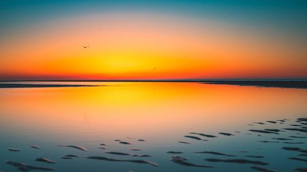 Prachtig uitzicht op de weerspiegeling van de zon in het meer gevangen in vrouwenpolder, nederland